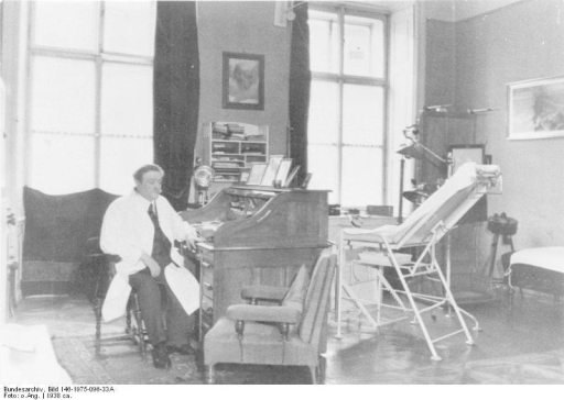 Dr Eduard Bloch, Chief Medical Director of Health (GP Hitler family), in his consulting room in Linz.From the German Federal Archive, Bild 146-1975-096-33A/O. Ang., reused under the Creative Commons Attribution-Share Alike 3.0 Germany license.