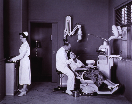 <p>Interior view: Ritter chair, dental unit, and x-ray machine.  A dentist, sitting on a stool, with a drill in his hand is working with a patient.  A woman in a white uniform is standing in front of a piece of equipment.</p>