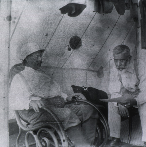 <p>Seated on bench inside tent, leaning forward, arms on knees, full face; Major LaGarde seated to the left in arm chair; wearing helmet;</p>