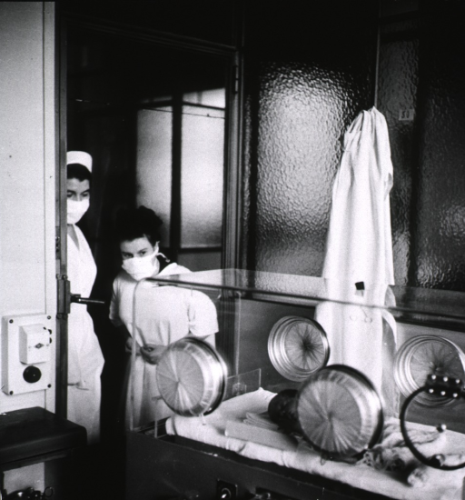 <p>Interior view: a nurse and the mother of a premature baby are standing at the entrance to the ward for premature babies; her baby is in an incubator that is near the entrance to the ward. A sterilized mask and gown must be worn while in the ward.</p>