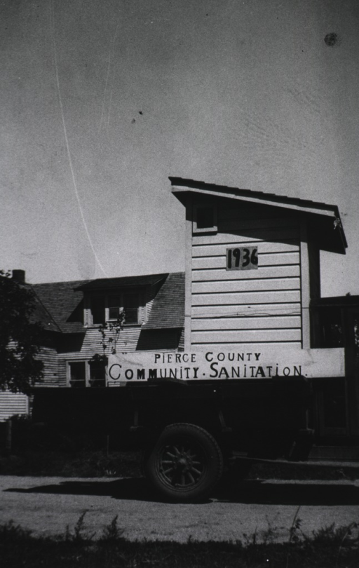 <p>Exterior view: a model privy stands on the bed of a truck; sign on the side of the truck reads, &quot;Pierce County Community Sanitation,&quot; and the date &quot;1936&quot; appears on the side of the privy; there is a house in the background.</p>