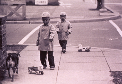 <p>Two children are playing with pull toys on the sidewalk.</p>