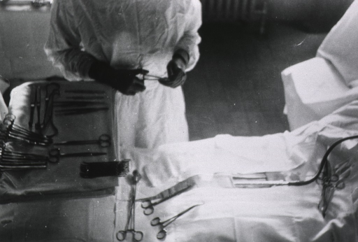 <p>Operating room, showing nurse handling instruments, as if preparing for operation.</p>