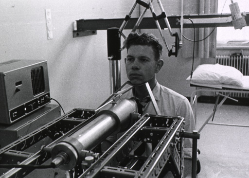 <p>Interior view: a young man is sitting before a piece of medical equipment that is focused on his throat.</p>