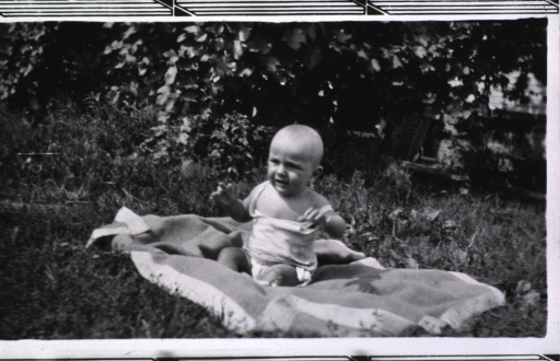 <p>Showing the baby, Elmer, sitting on a blanket enjoying the sunshine.</p>