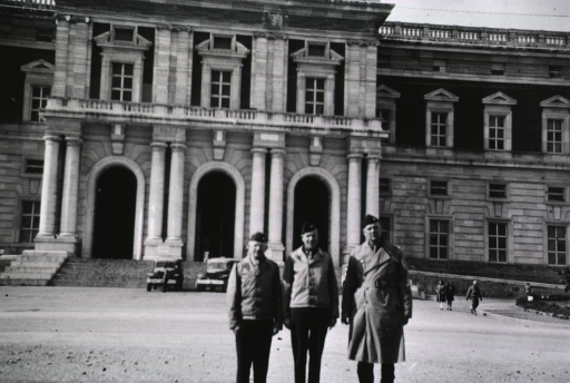 <p>The three servicemen stand in uniform in front of a two-story building serving as the 17th General Hospital.</p>