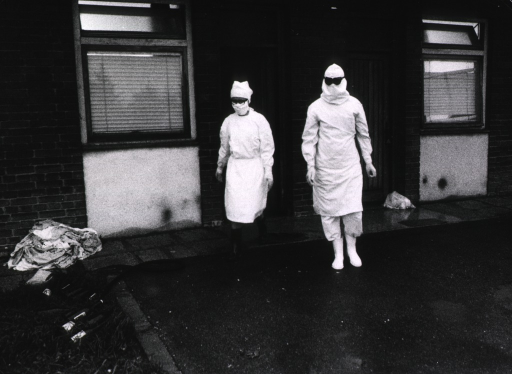 <p>Two members of the hospital staff are wearing protective clothing, from boots, gloves, and caps to face masks and goggles.</p>