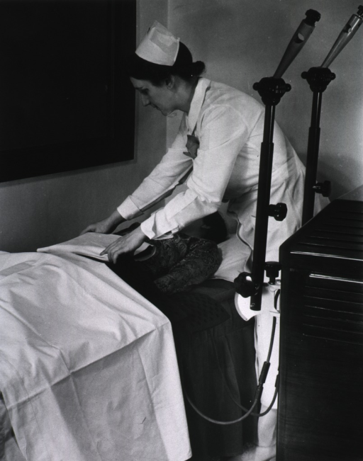 <p>A nurse attaches a patient to a machine while the patient is lying down in an office(?)</p>