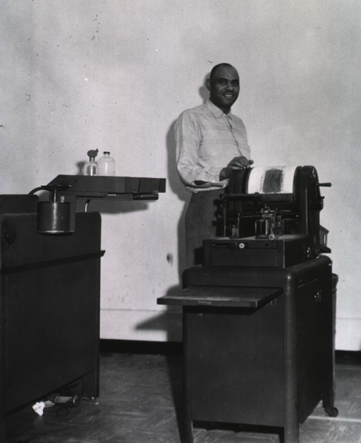 <p>Interior view: A man is standing next to a mimeograph machine.</p>