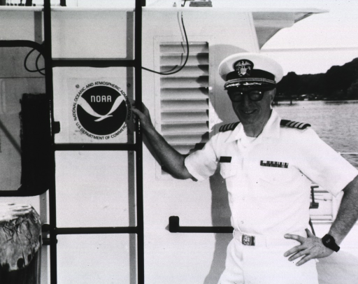 <p>Half-length, standing, wearing uniform, cap, and glasses; right hand on ladder next to the NOAA emblem.</p>