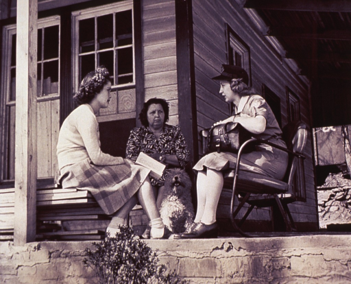 <p>A public health nurse talks to a young woman and her mother about childbirth; they are sitting on a porch.</p>