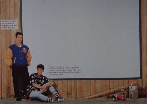 <p>Multicolor poster with black lettering.  Visual image is a color photo reproduction featuring two teen boys sitting and standing in front of a fence or wall.  The wall is blank.  The seated boy speaks the title text.  The boy who stands replies and asks what the viewer thinks.  Publisher information in lower left corner.</p>
