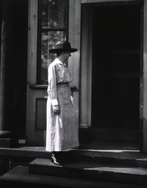 <p>A nurse stands on the outside steps of a building.</p>