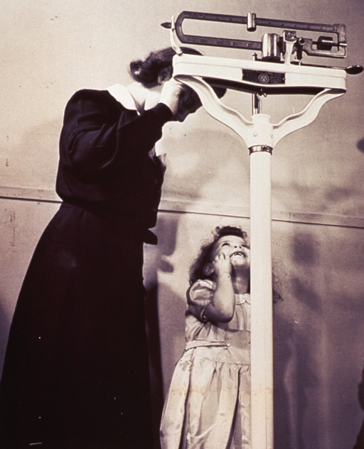 <p>A small child is standing on a scale.</p>
