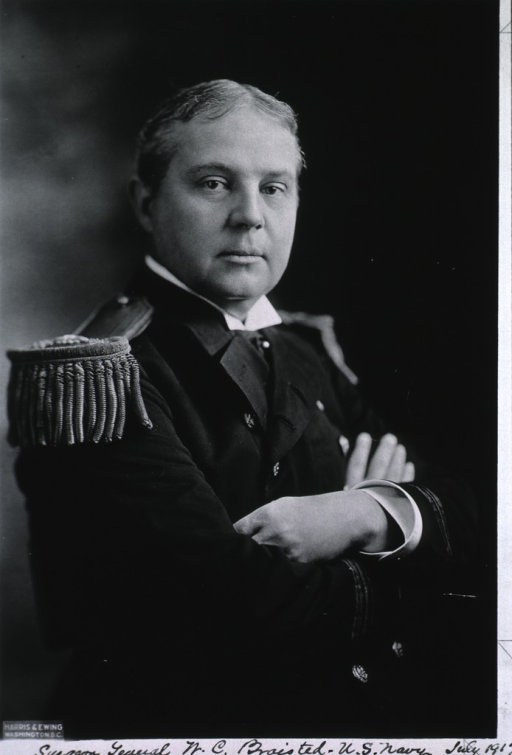<p>Seated with hands folded across chest, wearing uniform with epaulets.</p>