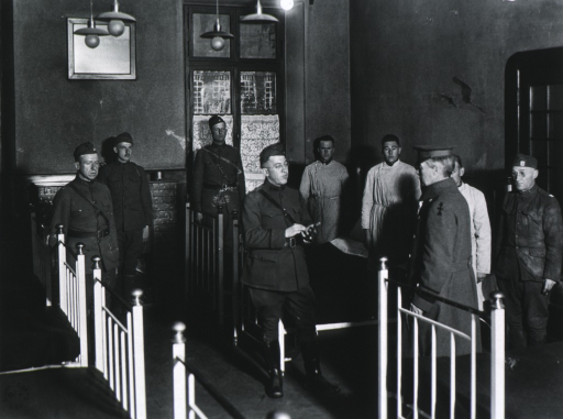 <p>Standing, full length; with group on inspection tour; talking with Major R.C. Perkins, C.O., Field Hospital 128, Sayn, Germany.</p>