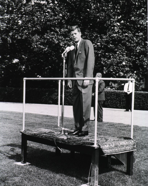 <p>Showing President Kennedy full length, standing on platform with microphone.</p>