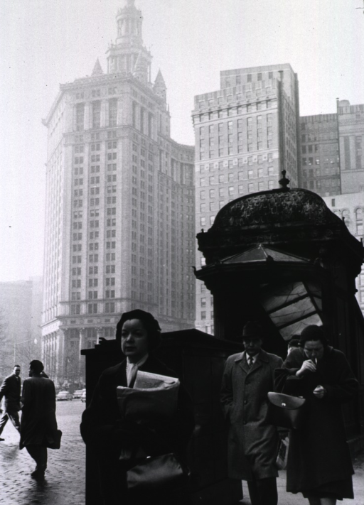 <p>Street scene near the entrance to the subway; a few people in the foreground, tall buildings in the background.</p>
