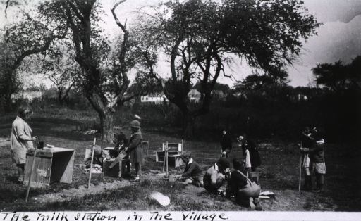 <p>Outdoor scene showing several children constructing a &quot;milk station&quot;.</p>