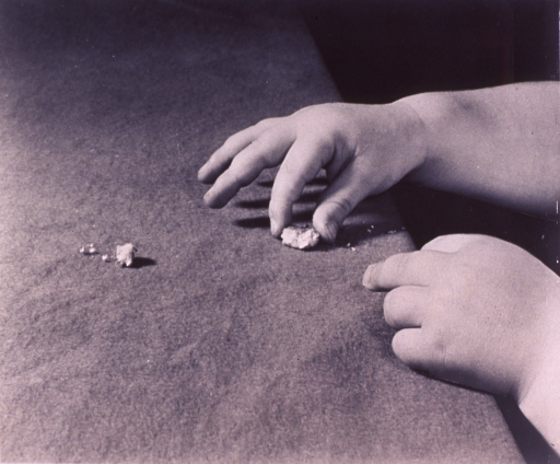<p>Hands attempting to pick up crumbs.</p>