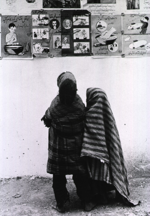 <p>Two children, viewed from behind, are looking at posters depicting healthy practices, that are hung on an exterior wall of a building.</p>