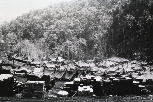 <p>View, from an adjacent hillside, of a group of pitched tents and army trucks laden with supplies.</p>