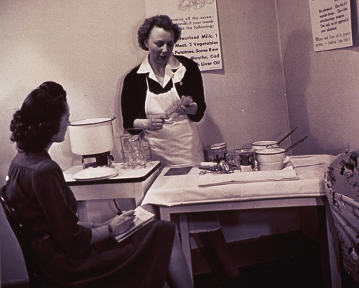 <p>A public health nurse instructs a young mother in the preparation of formula for her baby.</p>
