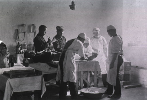<p>Surgeons treat a patients foot wound at Mukden Field Hospital, 5th Division, Japanese Army.</p>