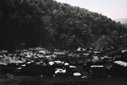 <p>View from an adjacent hillside, of a group of pitched tents and army trucks laden with supplies.  (This print is a reversed negative print of photograph no. 1 in this series.)</p>