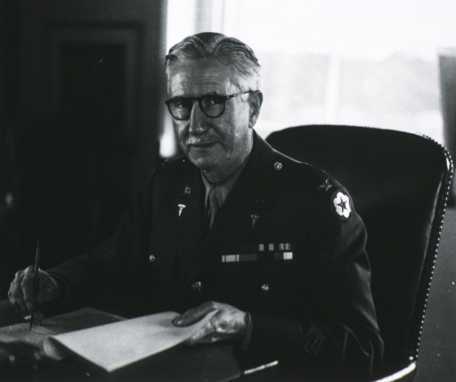 <p>Half-length, seated at desk, left pose, full face; wearing uniform and glasses; holding pen and papers.</p>