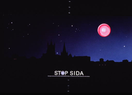 <p>Multicolor poster with white lettering.  Poster is predominantly a reproduction of a color photo of a city skyline, possibly Lausanne.  A church dominates the center of the photo.  An illustration of a fresh, pink condom is superimposed on the photo, as if to represent the moon.  Title and note at bottom of poster.  The &quot;o&quot; in stop is represented by a fresh condom.</p>