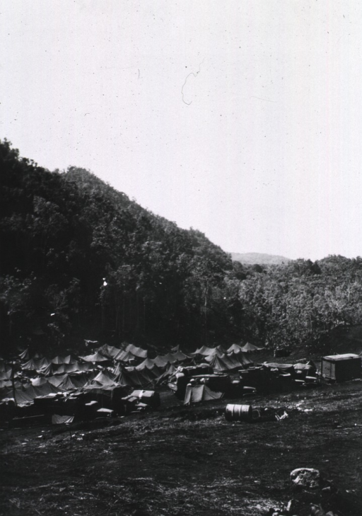 <p>View, from an adjacent hillside, of a group of pitched tents and army trucks laden with supplies.  (Cf. photograph nos. 1 and 2 in this series:  this print appears to be a reverse image print.)</p>