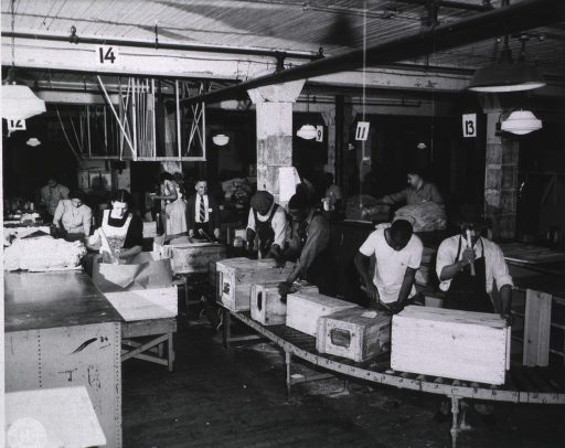 <p>African American men are standing behind a conveyor belt using hammers as they work with wooden boxes.  Women are standing beside wooden boxes with brown packing paper.  Linens are on the table in front of the women.</p>