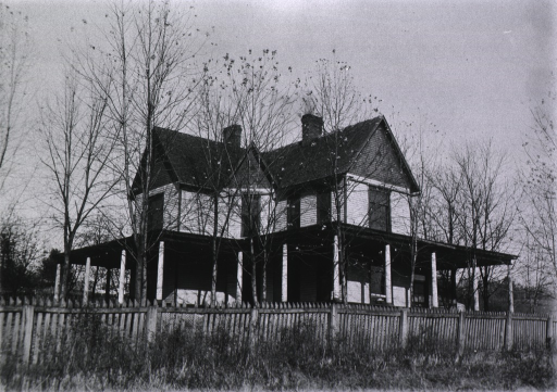 <p>Exterior.  Picket fence surrounding building.</p>