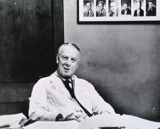 <p>Head and shoulders, full face, smiling, seated behind desk, in his office.  On the wall behind him, are autographed portraits of former students.</p>