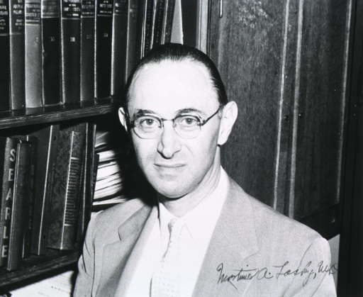 <p>Head and shoulders, left pose, full face; wearing glasses; bookshelves in background.</p>