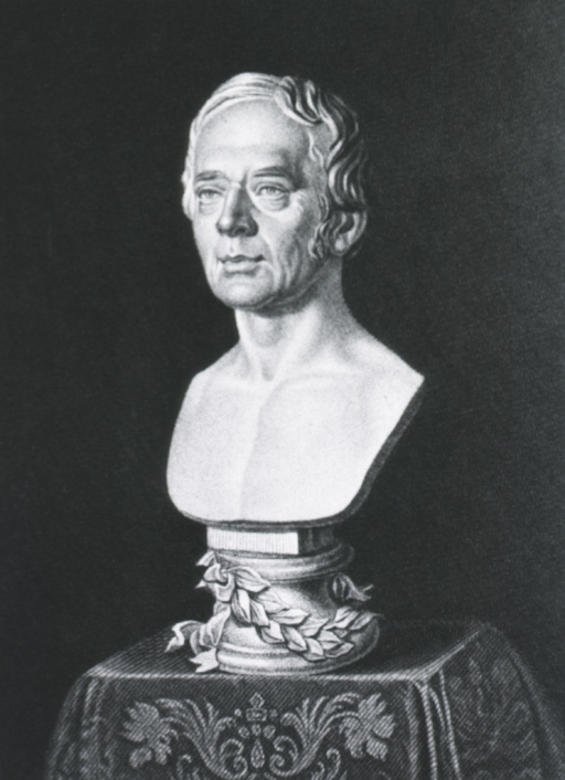 <p>Head and shoulders, full face; on table with wreath around base.</p>