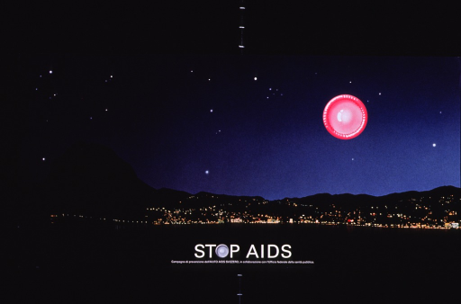 <p>The entire poster is a color photograph of a lighted city at night. A body of water is in the foreground and a mountain sits to the left of the city. A circular pink object is overlayed in the sky on the right side of the poster. The title and publisher/sponsor information (in white lettering) is at the bottom of the poster.</p>