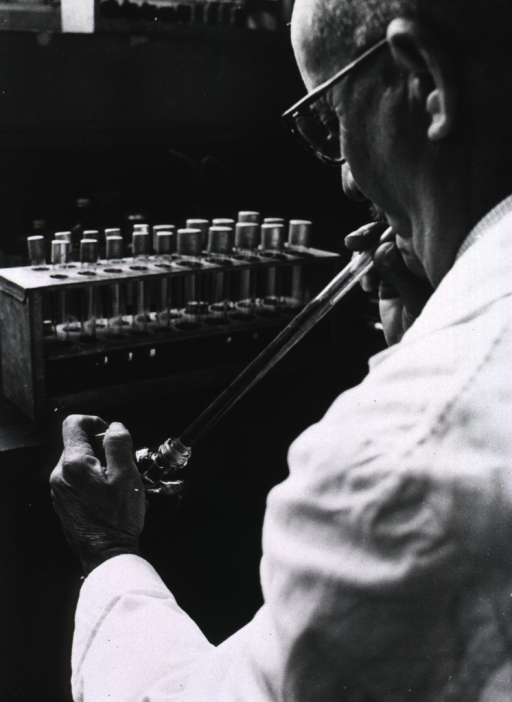 <p>Interior view of a laboratory: a man is drawing liquid into a pipette.</p>