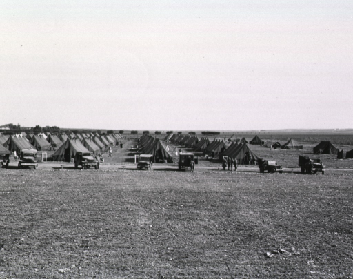 <p>Several long rows of tents are pitched on a flat field.  Military personnel are seen standing amidst the tents and around the army trucks that are parked next to the tents.</p>