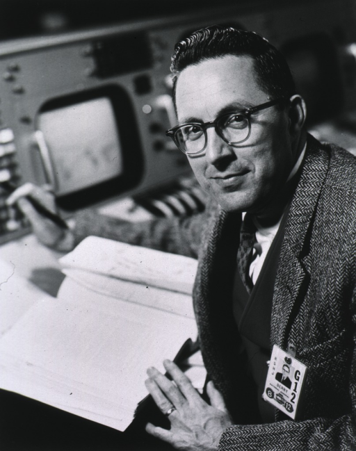 <p>Half-length, full face, wearing glasses, seated in front of electronic viewing equipment.</p>