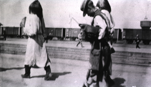 <p>A Chinese general walks ahead of two servants(?) at the railroad station in Harbin.</p>