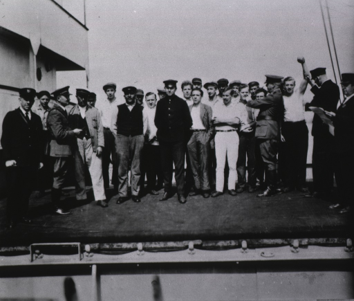 <p>A group of men on board a ship are being examined by medical examiners.</p>