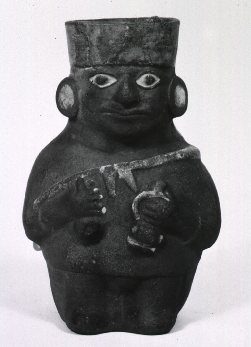 <p>Sculpture:  Urn of standing medicine man, draped in a shawl and holding a rattle and spouted drinking vessel in his hands.</p>