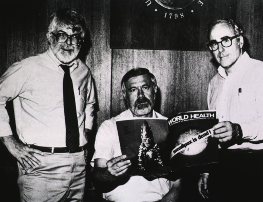 <p>Three men pose together, two of them are holding a copy of World Health magazine showing the cover which states that &quot;Smallpox is dead!&quot;</p>