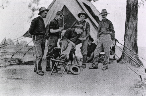 <p>Private McLin works on a patient outside his dental tent, while four men look on, one sitting near the tent.</p>