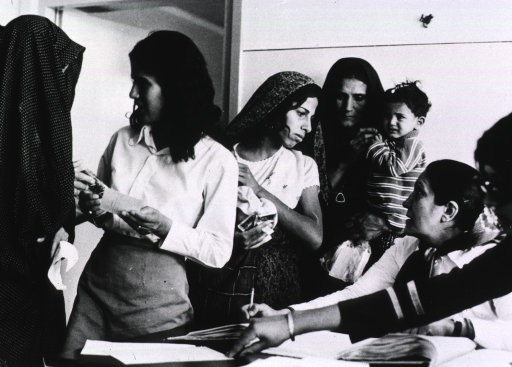 <p>Interior view: a group of women, some with children, are standing in the clinic talking to health workers.</p>