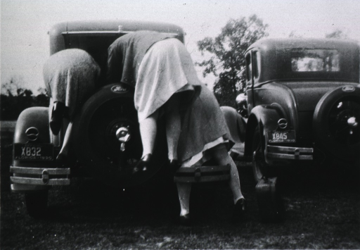 <p>View of the backs of three women bent over the trunk of a car.</p>