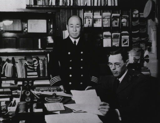 <p>Assistant Surgeon Joseph A. Bell examines the papers of the Japanese SS Shinyo Maru; the captain of the vessel stands at his desk observing the procedure.</p>
