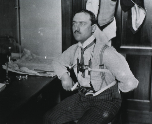 <p>Three-quarter length, seated, left pose; right arm resting on desk, left arm behind back.  Pneumograph attached for the experiment with Franz Muller's respiration apparatus for studying the volume of blood in the body.</p>
